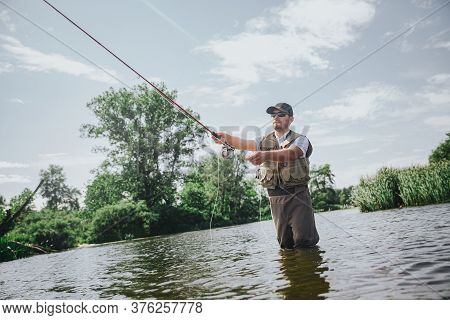 Young Fisherman Fishing On Lake Or River. Low View Of Guy In Rob Holding Long Rod And Using It For C