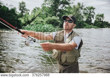 Young Fisherman Fishing On Lake Or River. Serious Concentrated Guy Holding Rod In Hands And Using It