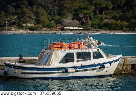 Small White And Blue Motor Boat With Orange Lifebelts On The Top, Moored In The Port Of Portovenere