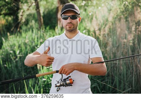 Young Fisherman Fishing On Lake Or River. Guy Stand Alone And Hold Big Thumb Up. Carry Long Rod With