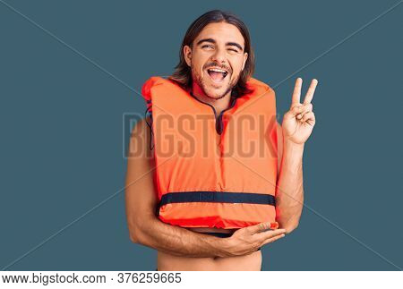 Young handsome man wearing nautical lifejacket smiling with happy face winking at the camera doing victory sign. number two.