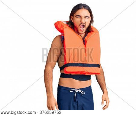 Young handsome man wearing nautical lifejacket winking looking at the camera with sexy expression, cheerful and happy face.