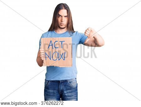 Young adult man with long hair holding act now banner with angry face, negative sign showing dislike with thumbs down, rejection concept
