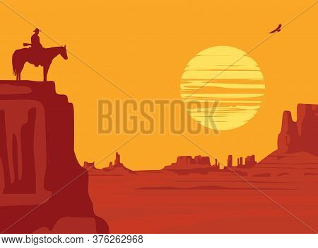 Western Landscape With Wild American Prairies And Silhouette Of A Cowboy Riding A Horse On Top Of A