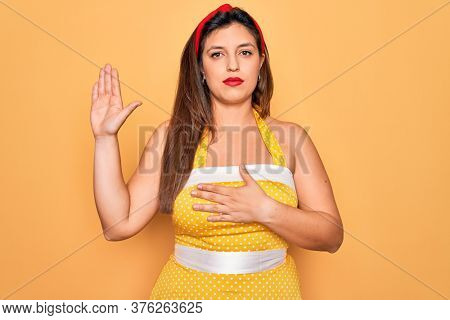 Young hispanic pin up woman wearing fashion sexy 50s style over yellow background Swearing with hand on chest and open palm, making a loyalty promise oath