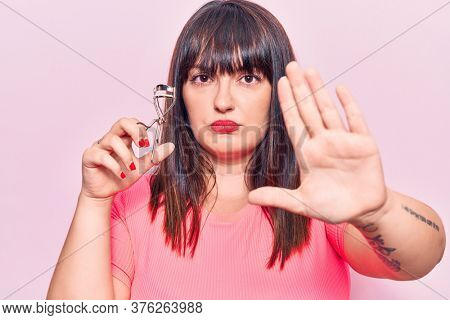 Young plus size woman holding eyelash curler with open hand doing stop sign with serious and confident expression, defense gesture
