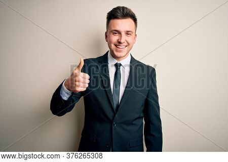 Young handsome business man wearing elegant suit and tie over isolated background doing happy thumbs up gesture with hand. Approving expression looking at the camera showing success.