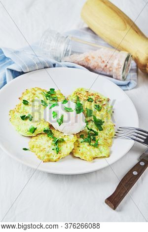 Vegetable Zucchini Pancakes With Poached Egg On White Plate