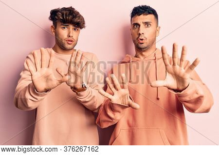 Young gay couple wearing casual clothes moving away hands palms showing refusal and denial with afraid and disgusting expression. stop and forbidden.