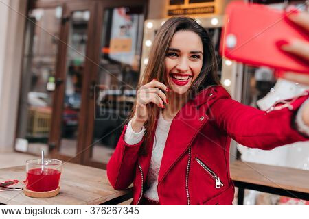 Lovable Girl With Pretty Smile Holding Red Phone And Making Selfie. Laughing Brown-haired Woman Taki
