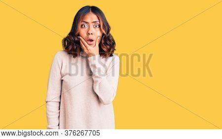 Young beautiful mixed race woman wearing winter turtleneck sweater looking fascinated with disbelief, surprise and amazed expression with hands on chin