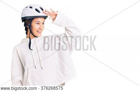 Beautiful brunette young woman wearing bike helmet and sporty clothes very happy and smiling looking far away with hand over head. searching concept.