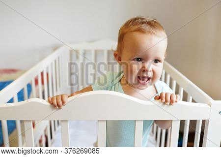 Beautiful Baby Standing In Crib. Portrait Of Cute Baby Girl Stand In Cot And Laughing