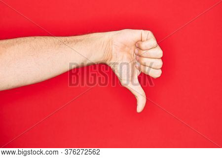 Hand of caucasian young man showing fingers over isolated red background doing thumbs down rejection gesture, disapproval dislike and negative sign
