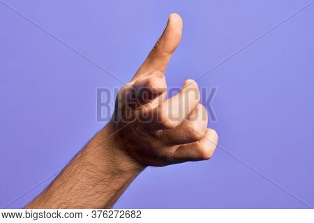 Hand of caucasian young man showing fingers over isolated purple background pointing forefinger to the camera, choosing and indicating towards direction