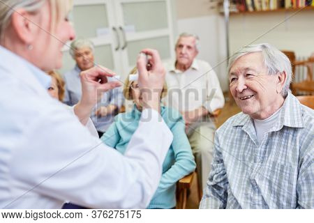 Doctor with dosing inhaler in a health consultation for senior citizens in a retirement home