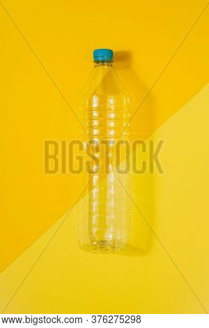 Vertical Color Image With An Overhead View Of A Clear Plastic Bottle With Blue Cap On A Yellow Backg