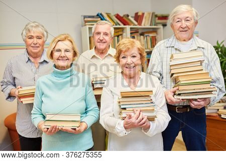 Group of seniors with a lot of books in the library of the senior residence