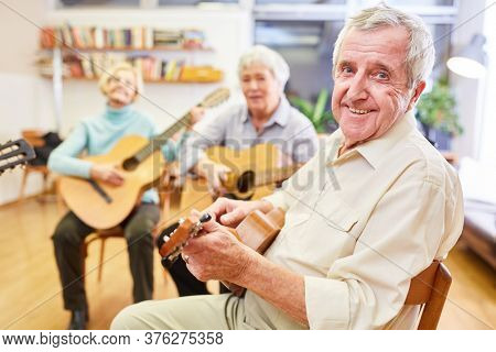 Senior man learns and practices playing guitar in a guitar course at the community college