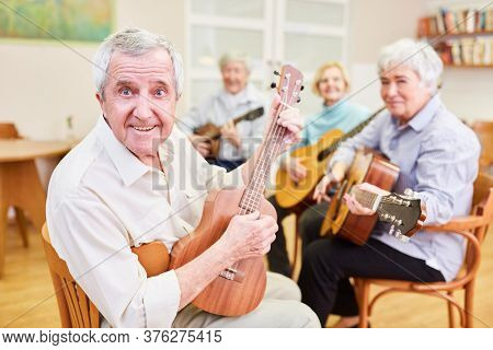 Senior as a guitar teacher with other seniors in a VHS guitar course