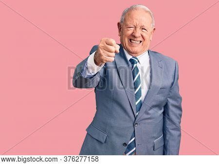 Senior handsome grey-haired man wearing elegant suit angry and mad raising fist frustrated and furious while shouting with anger. rage and aggressive concept.