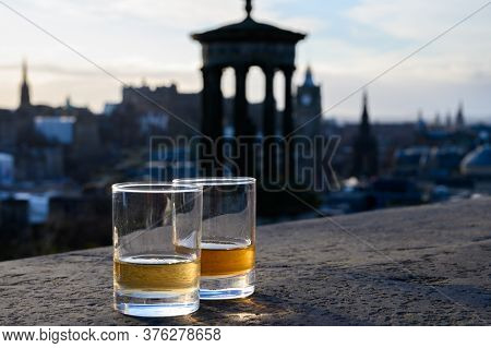 Scotch Single Malts Or Blended Whisky Spirits In Glasses With Calton Hill In Edinburgh On Background