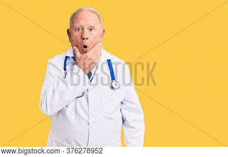 Senior handsome grey-haired man wearing doctor coat and stethoscope looking fascinated with disbelief, surprise and amazed expression with hands on chin