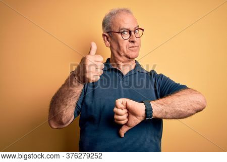 Middle age handsome hoary man wearing casual polo and glasses over yellow background Doing thumbs up and down, disagreement and agreement expression. Crazy conflict