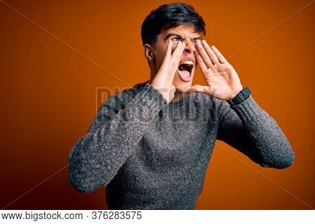 Young handsome man wearing casual sweater standing over isolated orange background Shouting angry out loud with hands over mouth