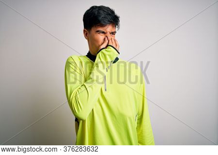 Young handsome sportsman doing sport wearing sportswear over isolated white background smelling something stinky and disgusting, intolerable smell, holding breath with fingers on nose. Bad smell