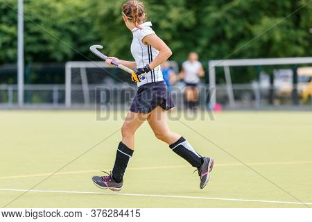 Young Woman Playing Field Hockey Game On The Pitch