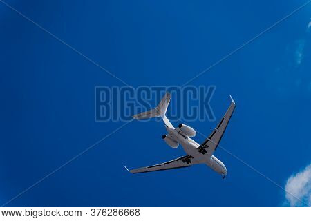Flying Plane Against The Blue Sky. A White Plane And An Indigo Sky. Airliner Before Landing With The