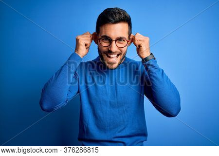 Young handsome man with beard wearing casual sweater and glasses over blue background Smiling pulling ears with fingers, funny gesture. Audition problem