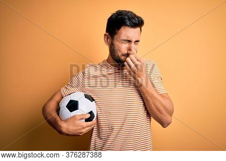 Handsome player man with beard playing soccer holding footballl ball over yellow background smelling something stinky and disgusting, intolerable smell, holding breath with fingers on nose. Bad smell