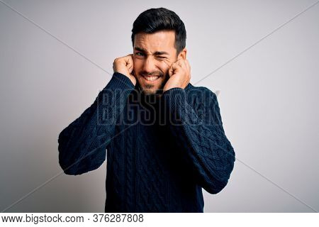 Young handsome man with beard wearing casual sweater standing over white background covering ears with fingers with annoyed expression for the noise of loud music. Deaf concept.