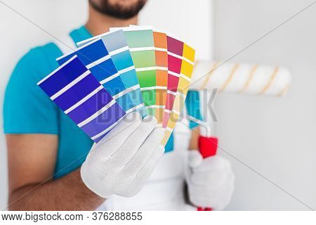 Crop Anonymous Male Interior Decorator In Uniform And Gloves Holding Paint Roller And Demonstrating