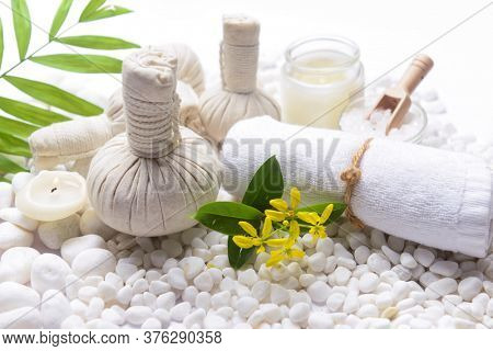 Spa setting with Green palm, bottles of essential oil with , herbal ball, salt in bowl ,candle , herbal ,ball ,spoon on pile of white stones ,yellow f orchid flower,,green palm