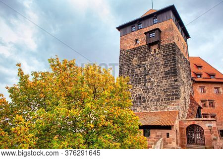 German Tower Made By Bricks . Medieval House With Tower And Attics