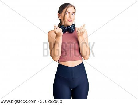 Beautiful caucasian young woman wearing gym clothes and using headphones doing money gesture with hands, asking for salary payment, millionaire business