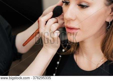 Makeup On The Face Of A Woman In A Beauty Salon Makes A Make Up Artist Hand With A Brush