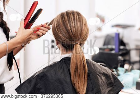 Hairstylist Makes A Hairstyle For A Woman With Light Brown Long Hair