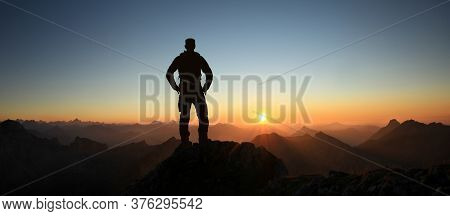 Man Silhouette Reaching Summit Enjoying Freedom And Looking Towards Mountains Sunset. Allgau Alps, B