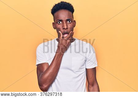Young african american man wearing casual clothes looking fascinated with disbelief, surprise and amazed expression with hands on chin