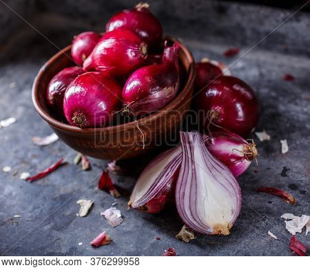 A Bunch Of Red Onions In A Clay Bowl. Cut Onion In Half On A Gray Texture Board.