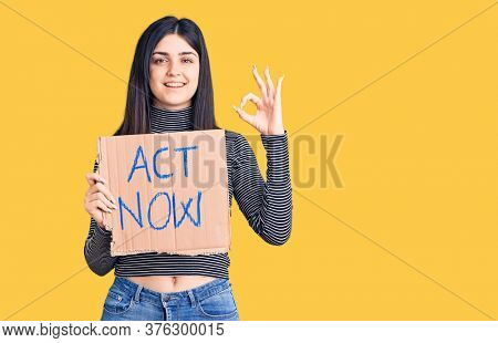 Young beautiful girl holding act now cardboard banner doing ok sign with fingers, smiling friendly gesturing excellent symbol