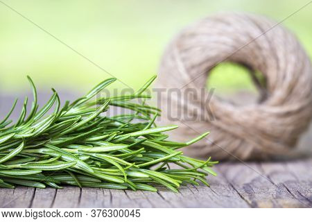 Fresh Green Herb Rosemary And Jute Twine Roll On A Wooden Table With Copy Space