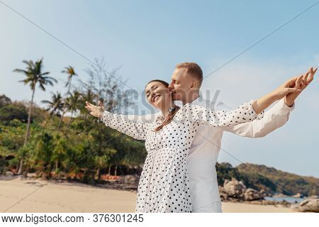 Happy Couple Standing By The Sea Arms Outstretched At The Beach.