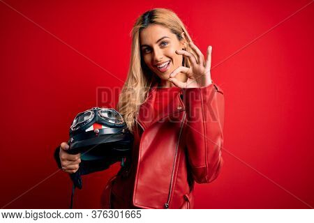 Young beautiful blonde motorcyclist woman holding moto helmet over isolated red background doing ok sign with fingers, excellent symbol