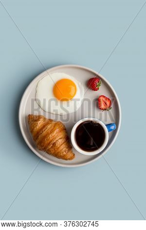 Simple Breakfast At Light Blue Background With Fried Egg, Croissant, Strawberry And Black Coffee In