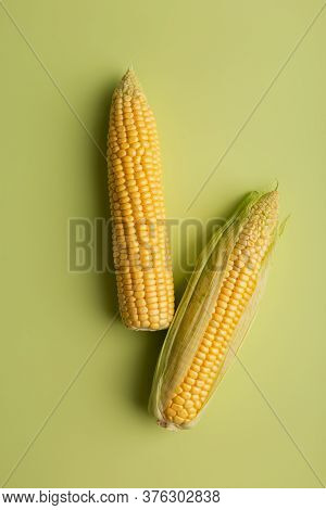 Fresh Two Corn Cobs At Green Minimal Background. Top View, Flat Lay, Copy Space, Place For Text, Con